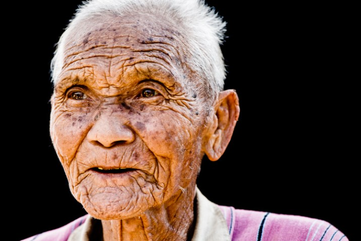 Portrait on a black background of a senior Pwo Karen man - how to use a reflector