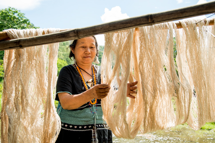 Hmong woman drying skeins of hemp thread outdoors - How to Use a Reflector to Improve Your Natural Light Portraits