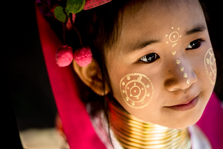 Close up of a Kayan long neck girl with traditional face painting, make-up