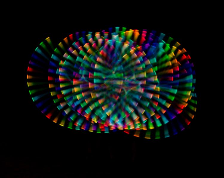 图片:火舞者使用彩色长条灯,并采取了更长的曝光时间以捕获纺纱...