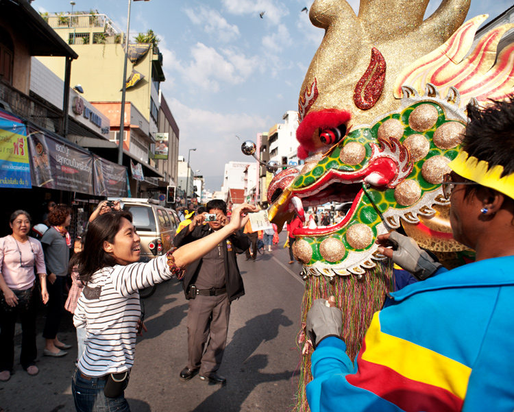 A woman places money in the mouth of a Chinese New Year dragon during a street parade in Chiang Mai, Thailand. - How to be Better Prepared for Your Next Photo Shoot