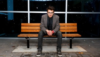 Portrait of man sitting at a bench, photographed with center composition and off-camera flash