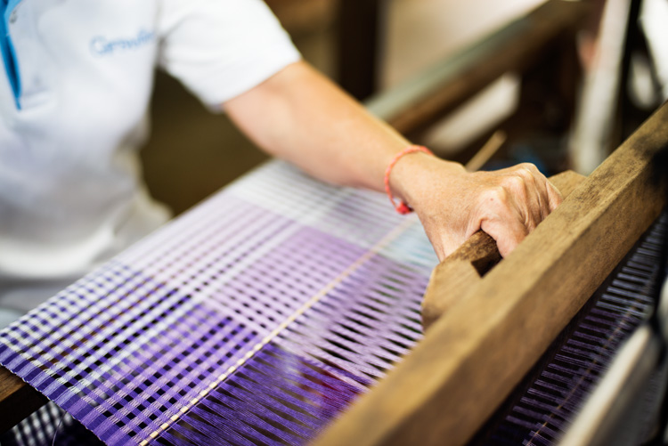 Thai woman working on a traditional loom weaving silk.