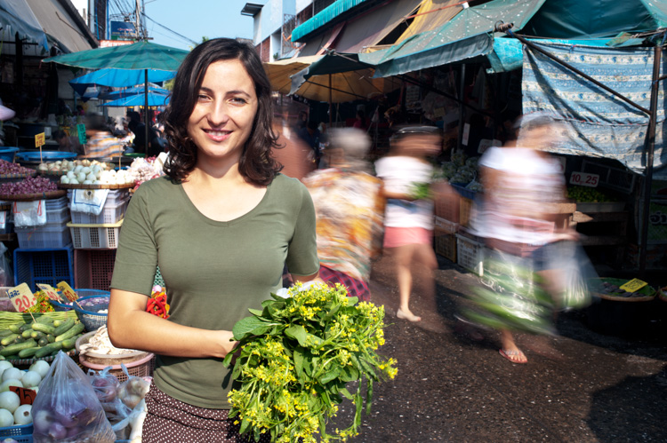 Woman standing in a fresh market holding vegetables - ISO 100