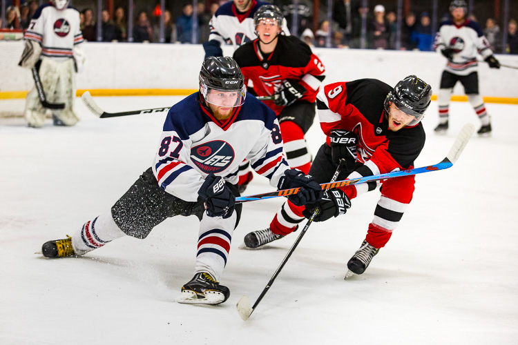 Two hockey players battle for the puck
