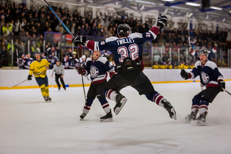An underexposed hockey image where the ice has turned a shade of gray - Tips for Editing Hockey Photos in Lightroom