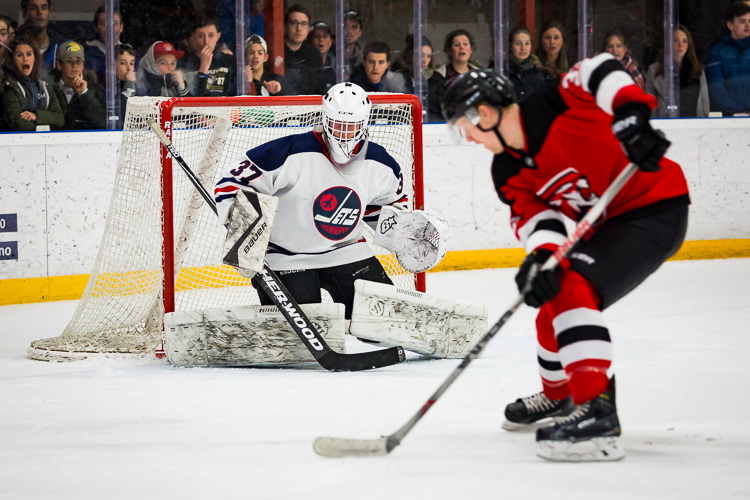 A hockey player on a breakaway against a goaltender - Tips for Editing Hockey Photos in Lightroom