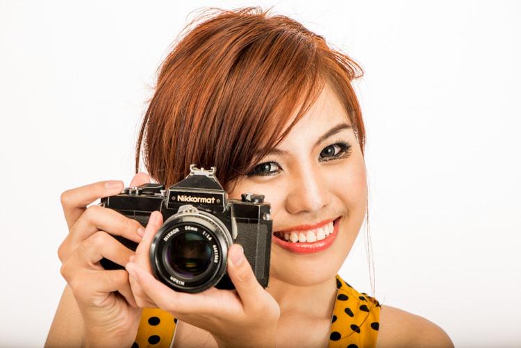 拿着一台老35mm影片照相机的亚裔妇女 -  4个技巧帮助您爱使用手动方式
