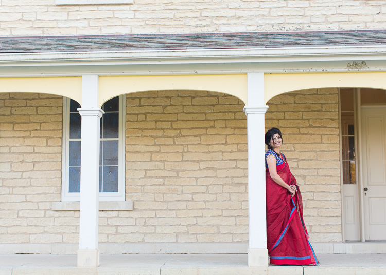Spot coloring in photography - woman in red sari against yellow brick house porch - 2