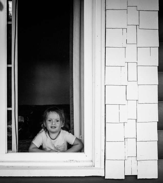 A little girl with her face pressed up to the window screen. How to Photograph Your Family Vacation