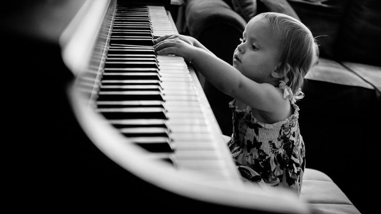 弹钢琴的一个小女孩。