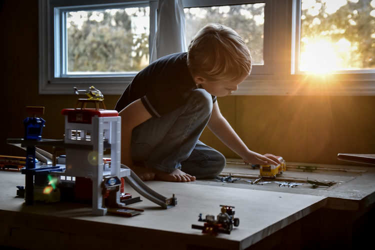 A child playing with toys indoors as the sun sets outdoors.