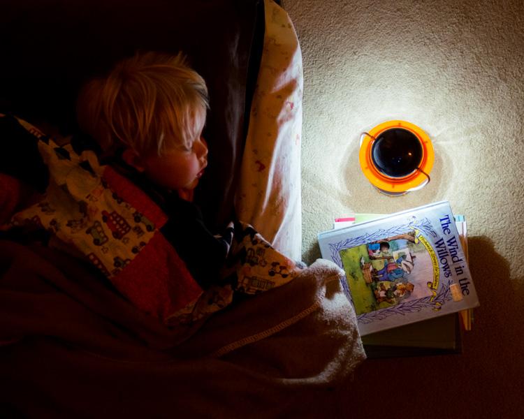 A boy sleeping with a latern.