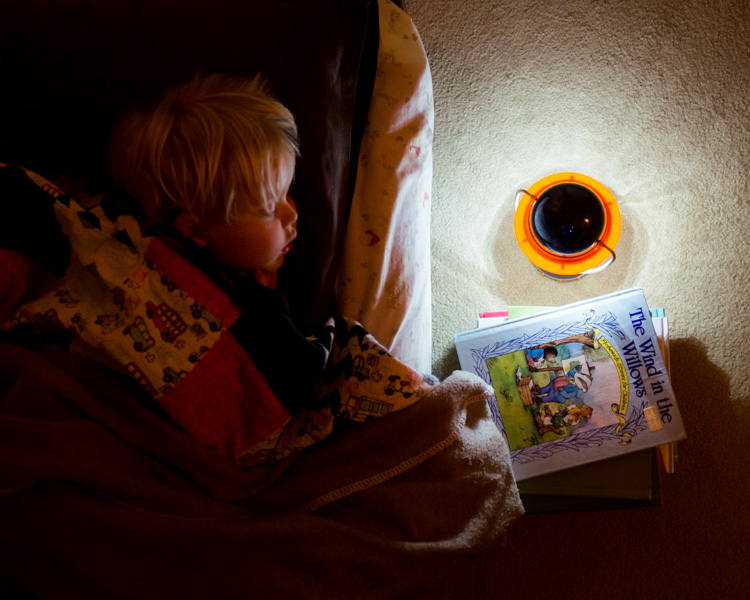 A boy sleeping with a latern.