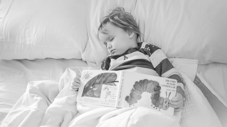A child sleeping with a book.