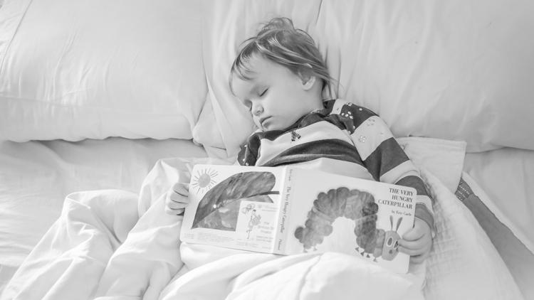 一个孩子和一本书睡觉。