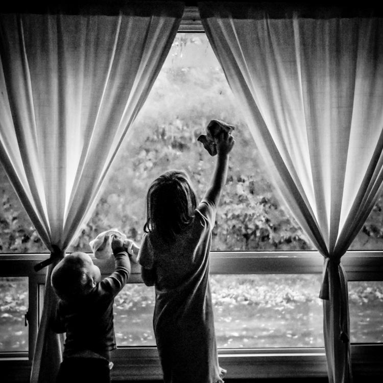 Boys washing a big window. family life