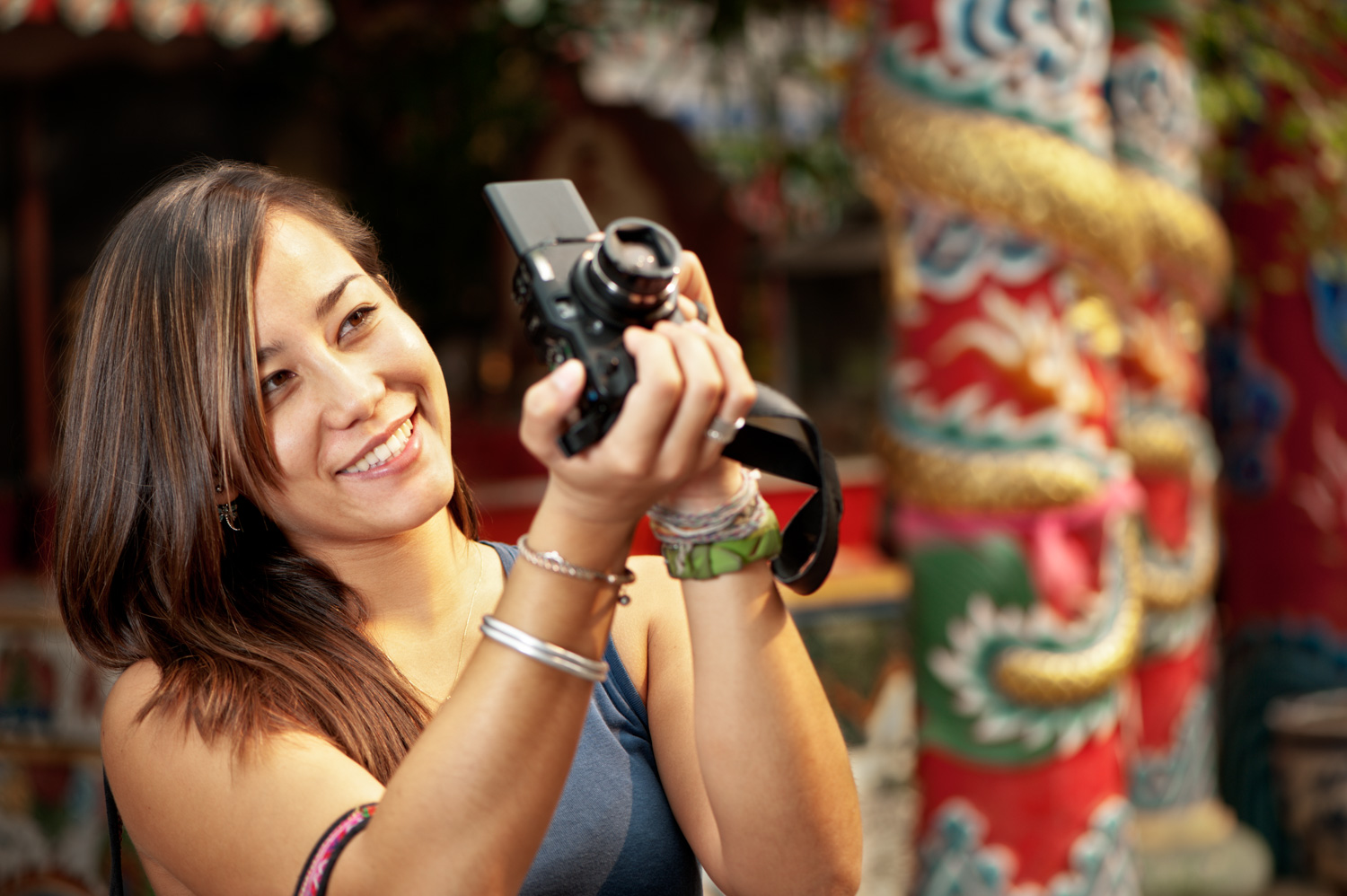 Asian woman with a camera - 4 Tips to Help You Overcome the Fear of Photographing People