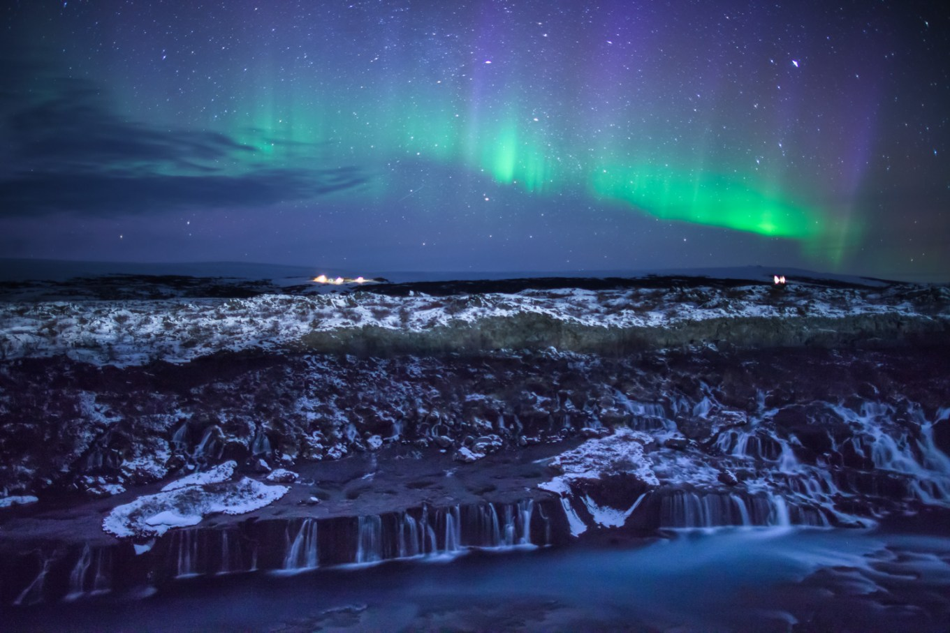Nighttime photography - northern lights over mountains and waterfalls
