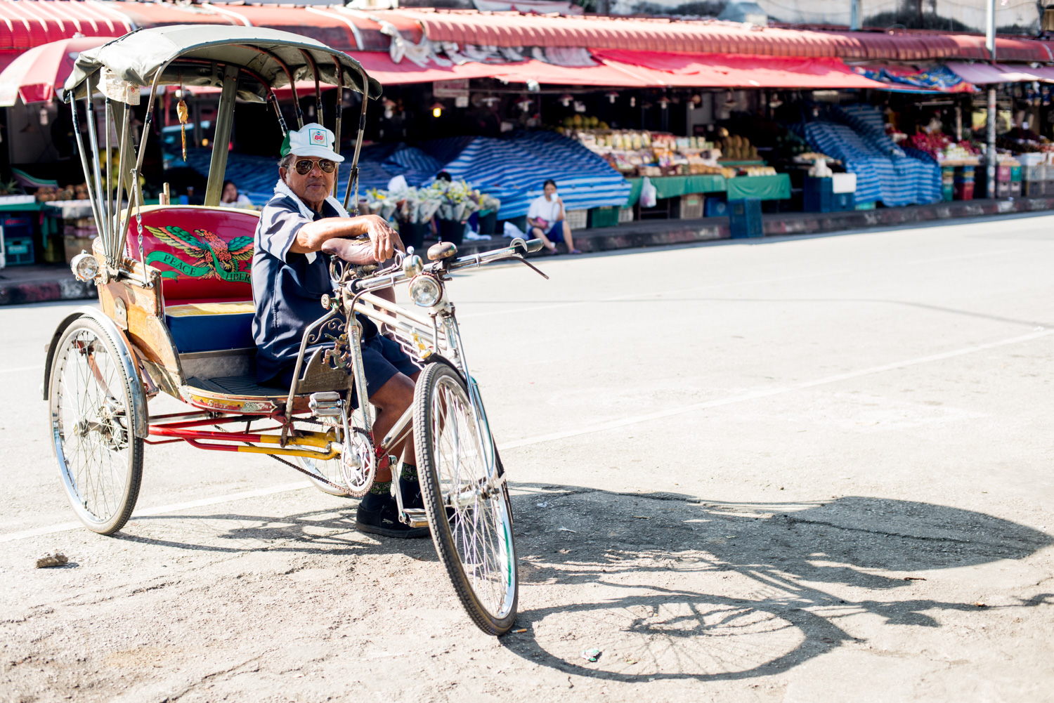 tricycle taxi and rider at a Thai market by Kevin Landwer-Johan (copyright) - 7 Tips for Avoiding a Distracting Background in Street Photography