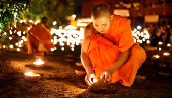 Buddhist monk lighting a candle during a night ceremony in Chiang Mai, Thailand © Kevin Landwer-Johan