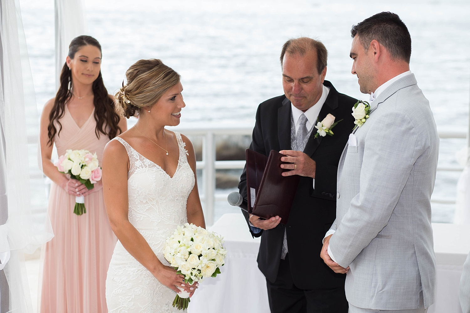 Image: The bride's father is the officiant and her sister is behind them.