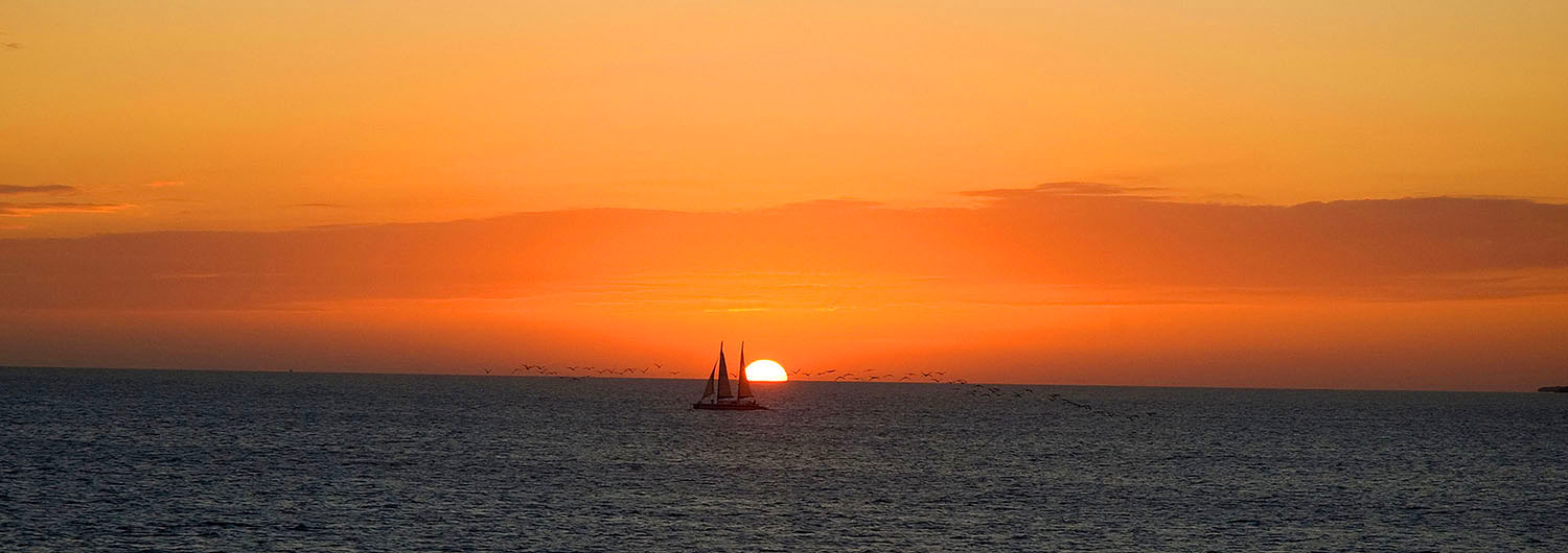 Image: The warmth of the orange skies delivers the beauty, calm, and warm stillness of the ocean at...