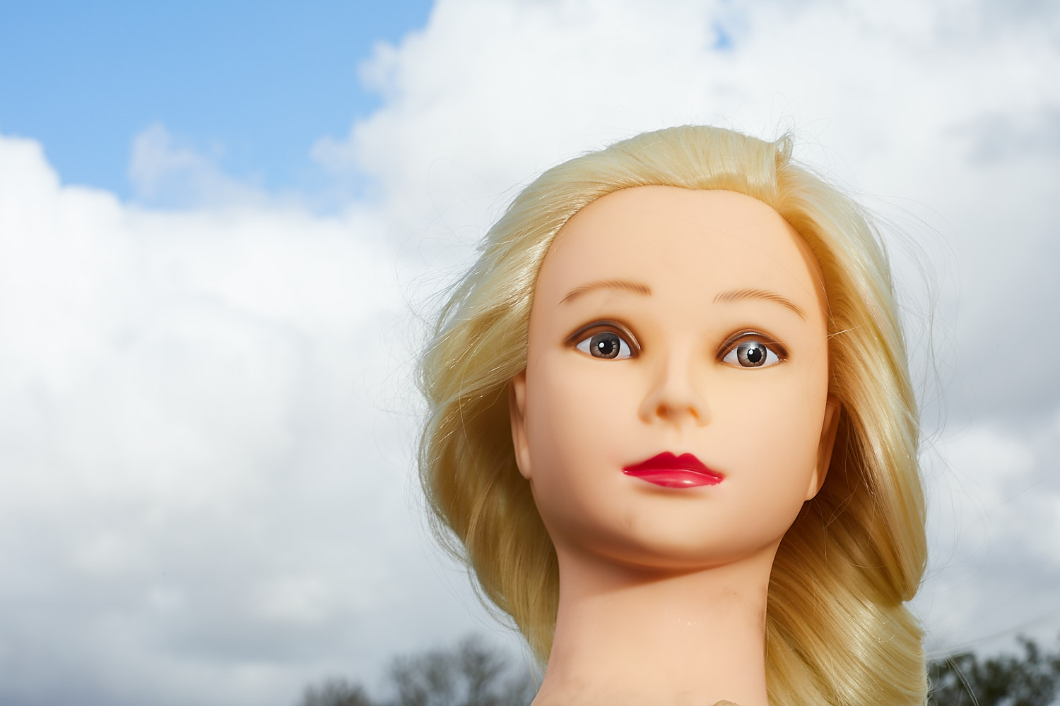 A photo off a mannequin used to illustrate getting started in off-camera flash. The doll is shot against a cloudy sky.