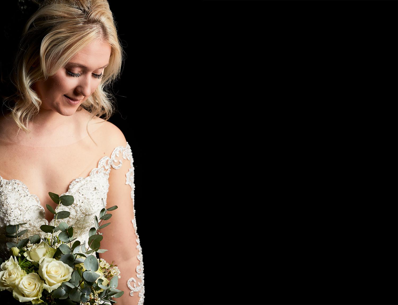 A model bride shot against a dark backdrop in a dimly lit venue.