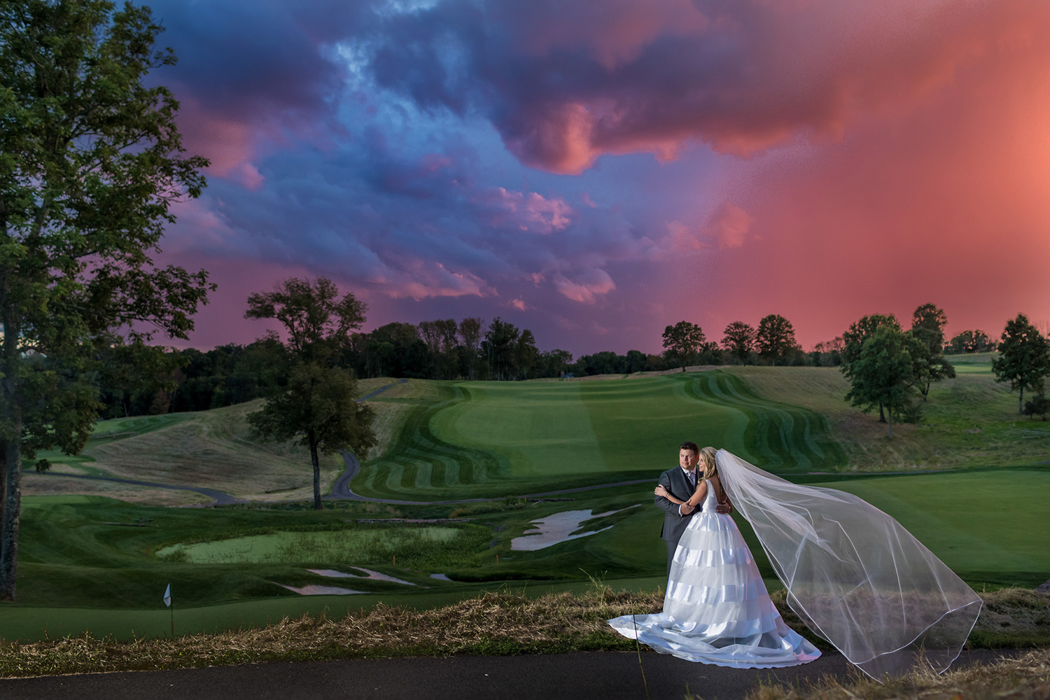 Canon Explorers of Light  – Q&A with Photographer Vanessa Joy. A bride and groom photographed against a pink and blue stormy sky and rolling green hills.