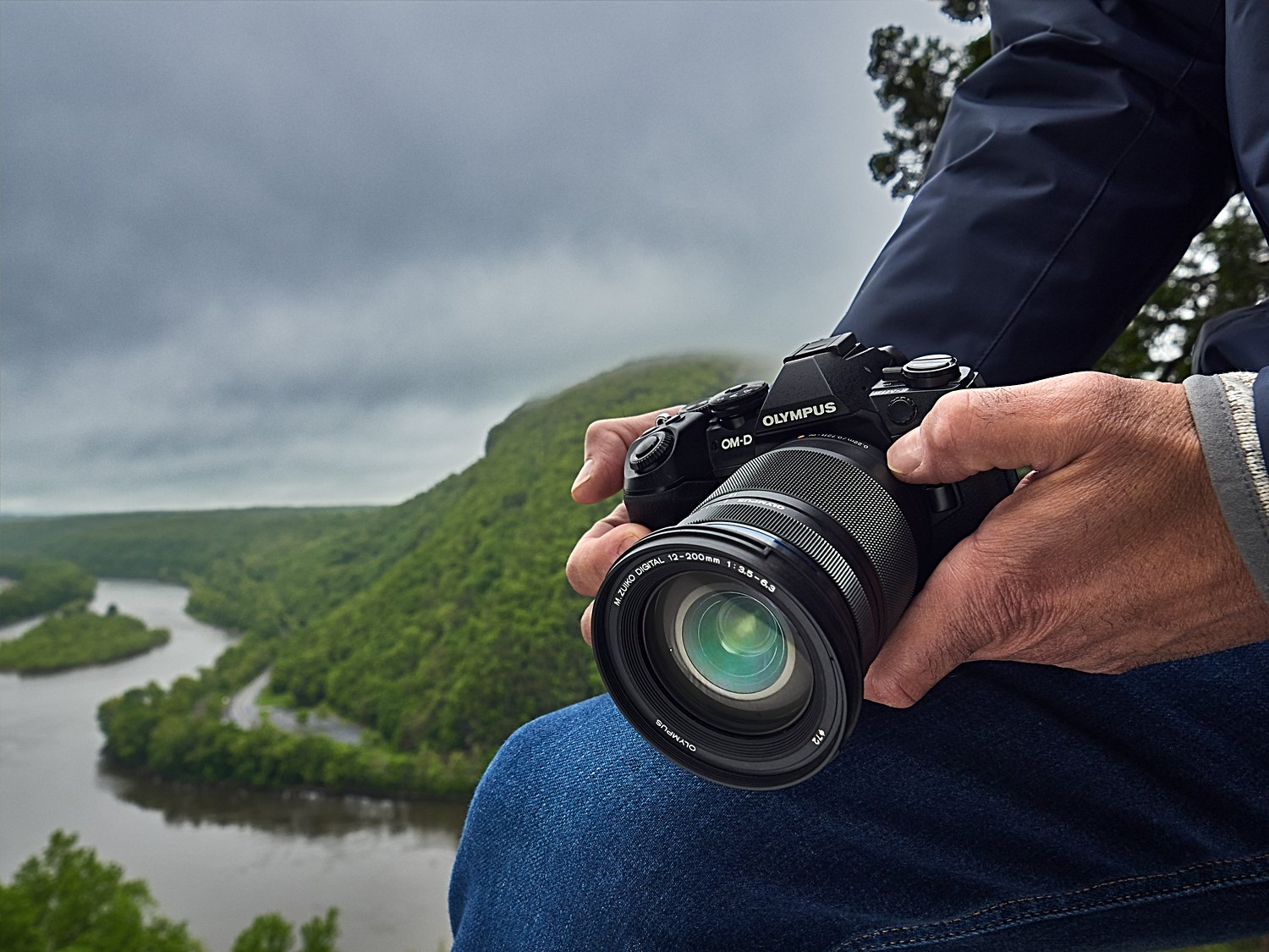 Person holding an Olympus mirrorless camera.