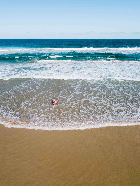 Uma pessoa que entra no surf na praia tirada por um drone