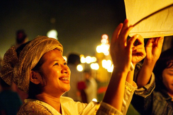 Person launching a sky lantern at the Loi Krathong festivlal in Thailand.