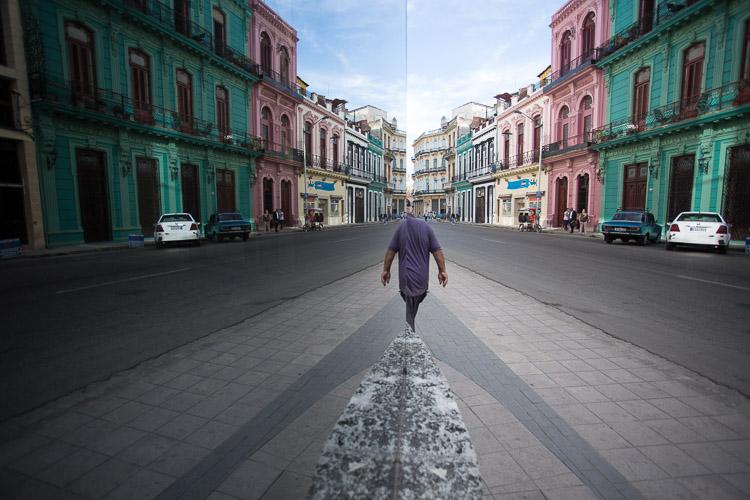 man walking past reflective window
