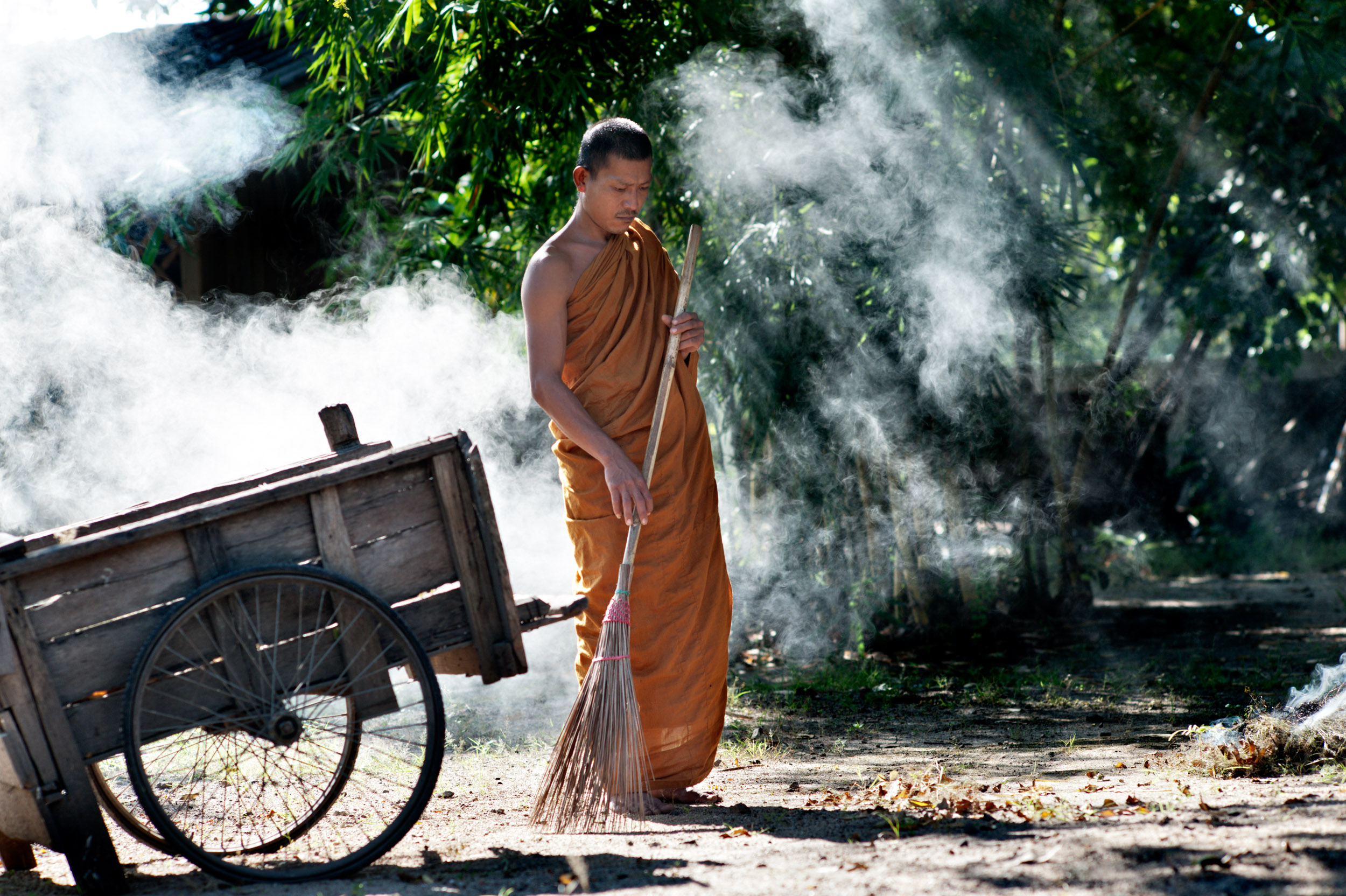 a monk sweeping leaves portrait photography idea