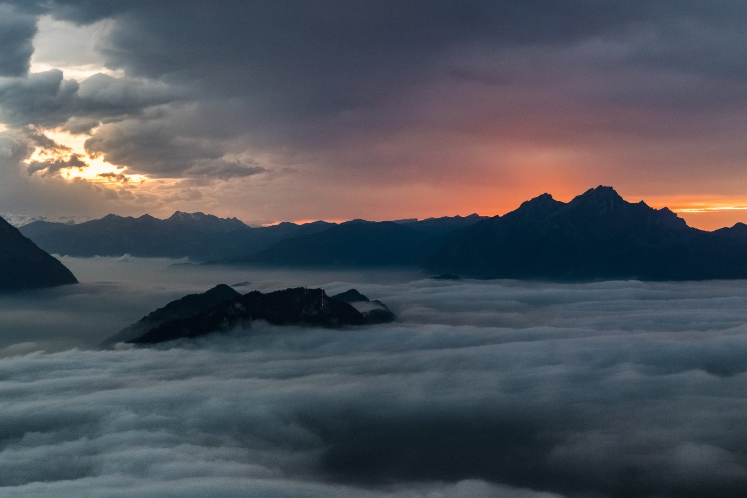 clouds below the mountains