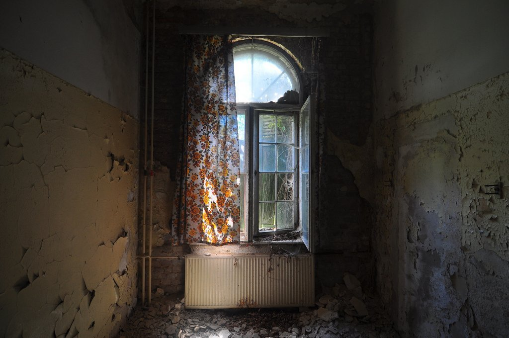 an abandoned room with orange flower curtains