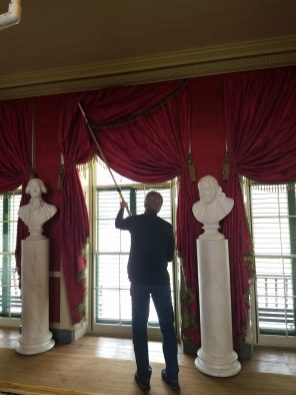 Staff member, Al, pushes back the Drawing Room curtains before removing the large storm windows.