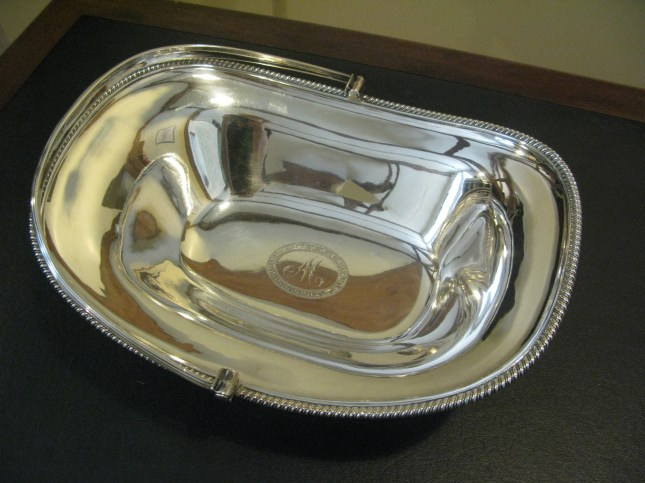 A silver cake basket with M monogram. LMF2009.2. Courtesy of Martha Madison Campbell. Handle down.