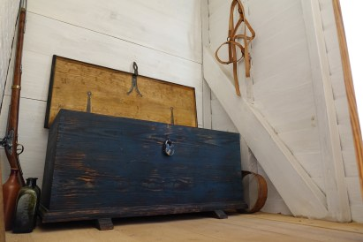View of the blanket chest in the southwest dwelling in the South Yard. Notice the harness hanging on the wall.