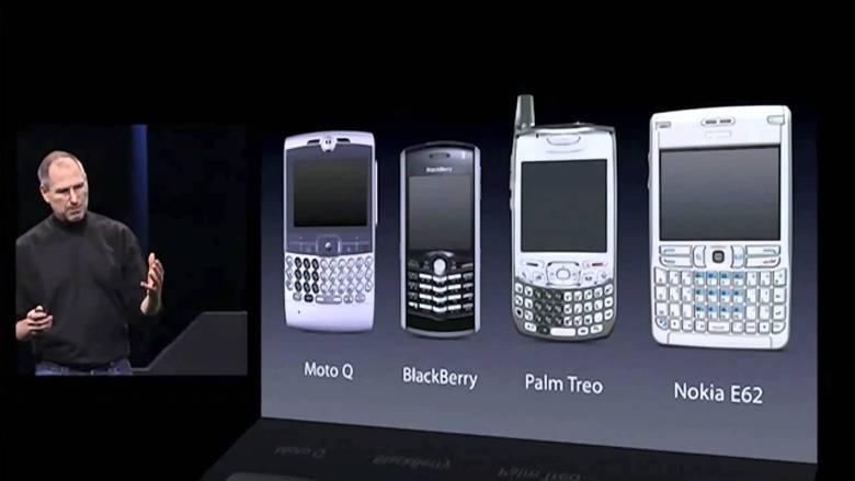 Steve Jobs legt den Finger in die Wunde. Ansicht von Tastaturhandys bei der Vorstellung des iPhones. Digitales Leben in Vergangenheit, Gegenwart und Zukunft