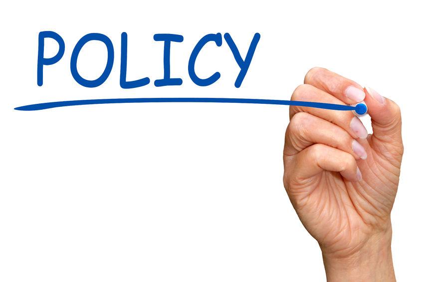A hand that is underlining the word Policy