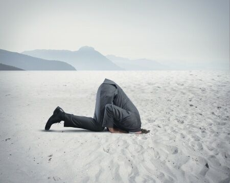 Concept of fear shown as businessman with head in the sand like an ostrich