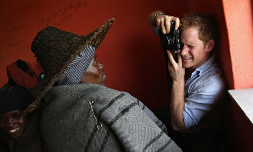Prince Harry takes a photograph during a visit to a herd boy night school