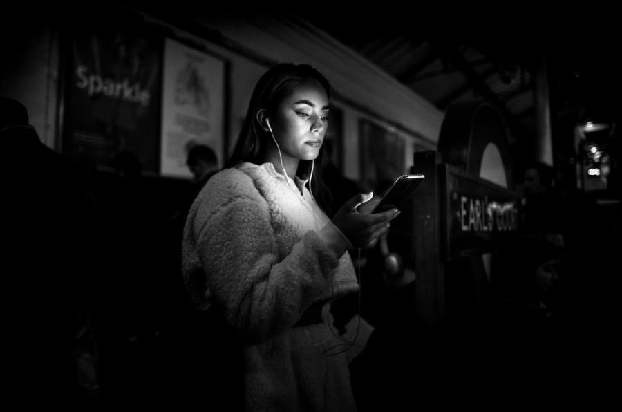 Foto tomada con Leica M10 Monochrom, chica mira su teléfono móvil.