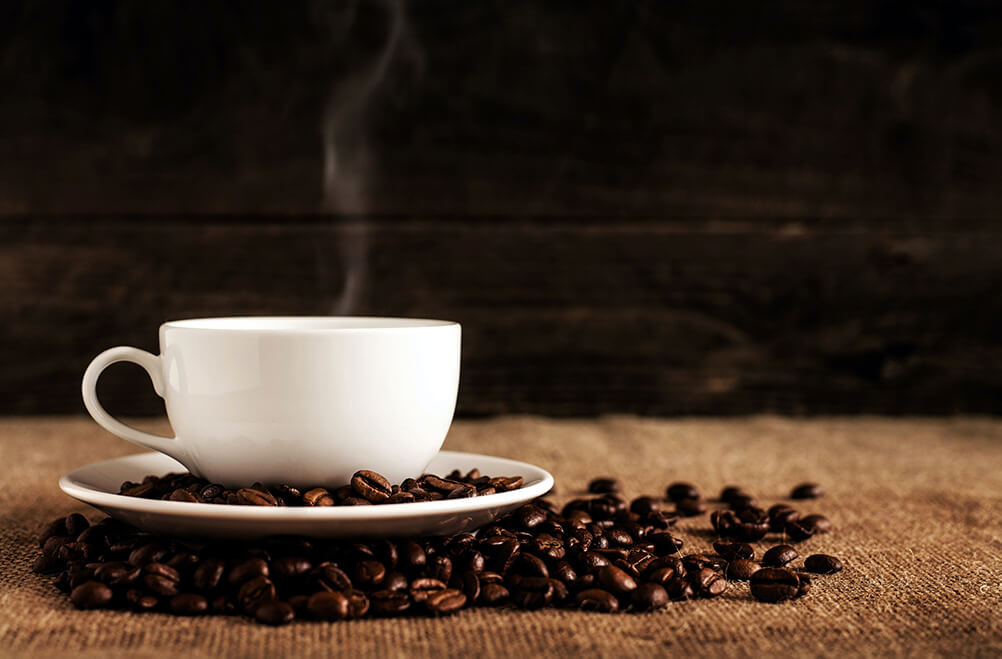 A cup of hot coffee surrounded by coffee beans