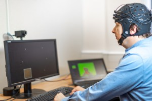 man sitting in-front of two computer monitors with head sensor son