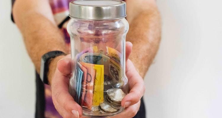 Personne qui tend un bocal contenant de l'argent