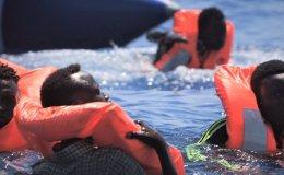 Des migrants dans la mer méditérranée avec des gilets de sauvetage