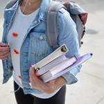 Une étudiante tenant ses cahiers sous le bras